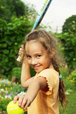 portrait of cute little girl playing tennis outdoors photo