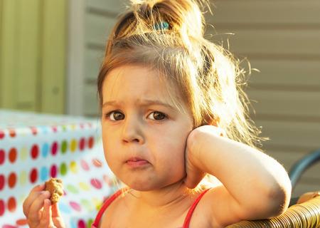 junk food: Sweet little girl eating cake at sunset