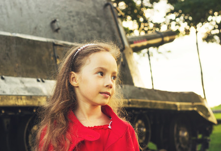 Toned  portrait of little girl near military tank at sunset photo