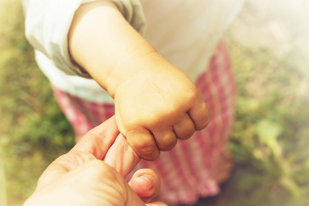 Parent holds the hand of a small child Stock Photo