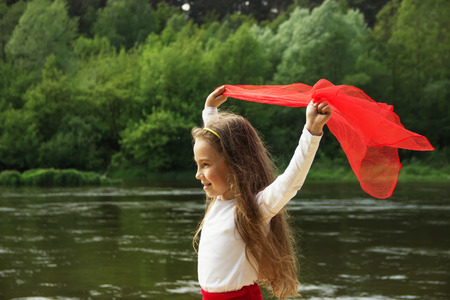 gentle dream vacation: Portrait of little cute girl dance with red Scarf by the river