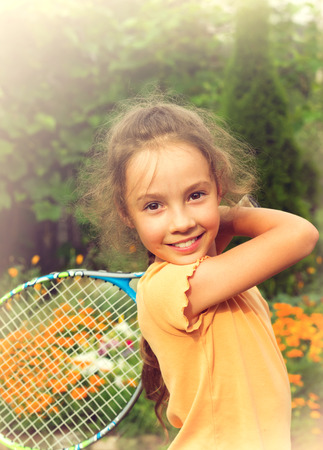 Toned portrait of pretty little girl playing tennis outdoors photo