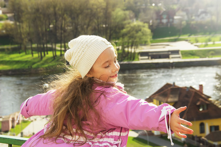 Cute child shone with happiness, curly hair, charming smile in the sunny spring day photo