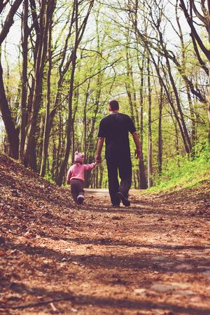 niños caminando: Retrato entonado de Padre e hija caminando en el bosque. Foto de archivo