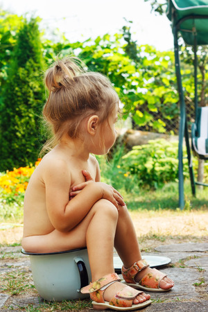 Cute Happy toddler sitting on potty outdoor