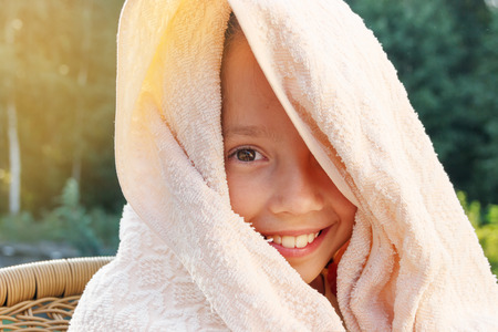 Cute little girl is drying off from swimming at summer day