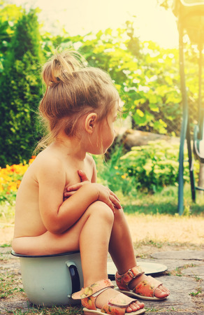 Toned portrait of Cute Happy toddler sitting on potty outdoor Stock Photo