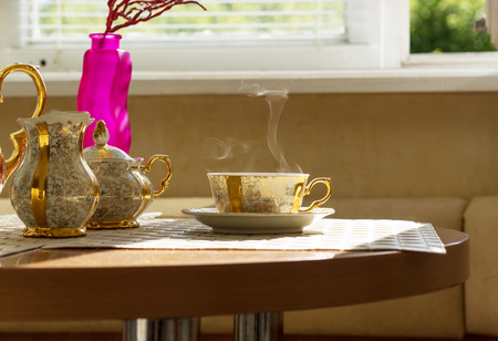 gilt: Gilt cup of coffee on table in cafe Stock Photo