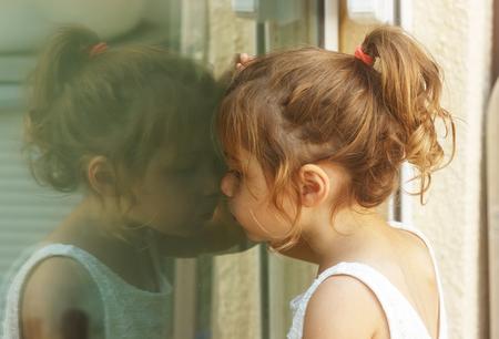 Thoughtful little girl looking through the window Foto de archivo