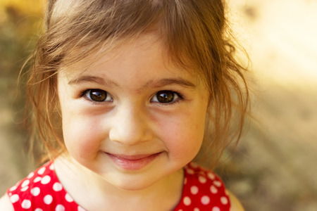 sunny season: Cute little girl smiling in sunny summer day outdoors