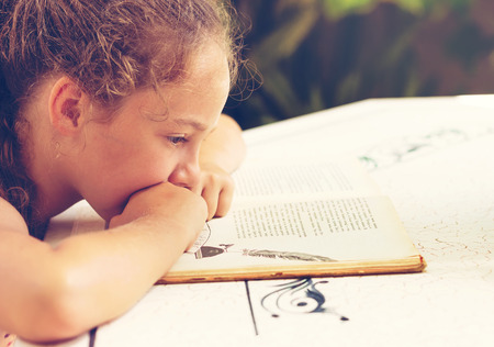 Toned Outdoor portrait of a cute little girl reading a book