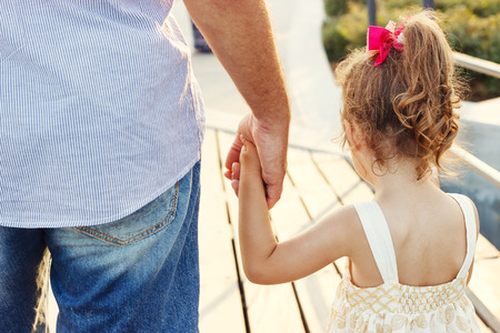 fathers: Father and daughter holding hand in hand at sunset Stock Photo