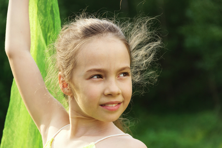 gentle dream vacation: Toned Portrait of little cute girl dance with green Scarf Stock Photo