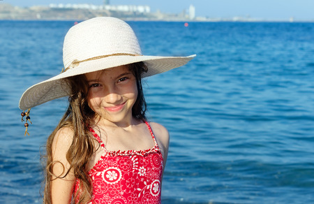 Cute little girl in hat relaxing on the sea, summer, vacation, travel concept.