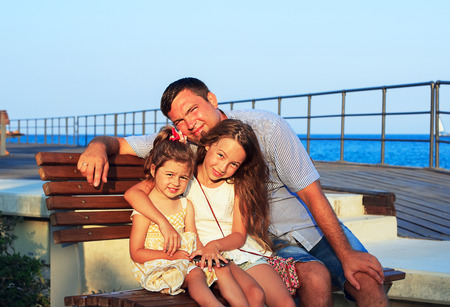 happy families: Father and Daughters Playing Together at the Beach at Sunset. Happy Fun Smiling Lifestyle. Dad with his Little Girls spending quality time Together Outdoors     Stock Photo