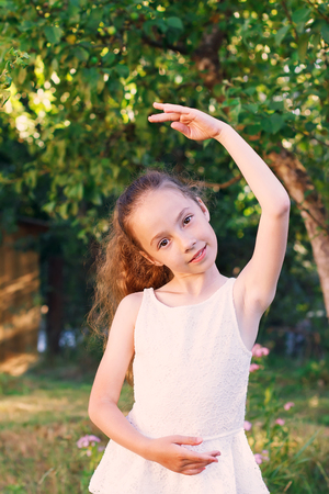 gentle dream vacation: Cute little girl dreams of becoming a ballerina. Child girl in white dress dancing outside.  Beautiful Preteen Girl is studying ballet. Stock Photo