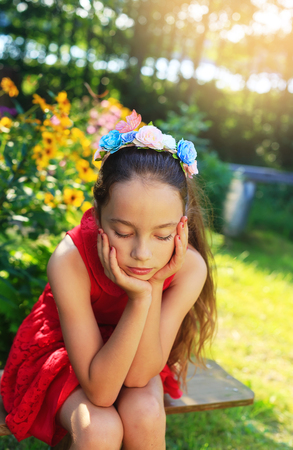 Beauty Sad Girl Outdoors dreaming at the garden. Beautiful Teenage girl with long hair smiling. Stock Photo