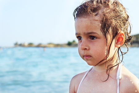 look latino: Cute Sad Little girl is looking at the wide sea at summer Stock Photo
