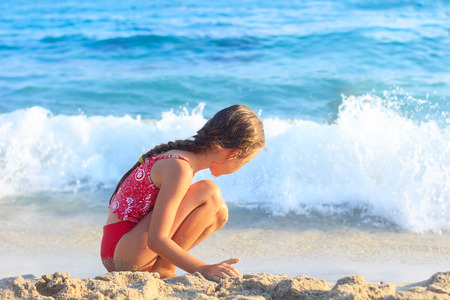 Happy Little Girl playing with sand by the Sea Waves.  Summer Sunny Day, Ocean Coast Stock Photo
