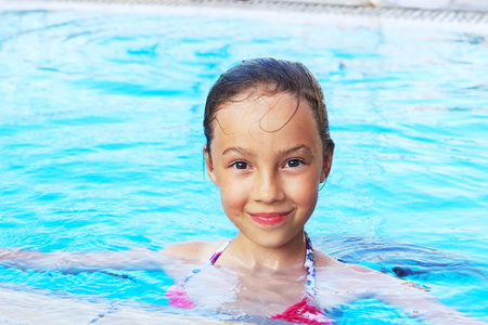 Cute little girl is smiling in swimming pool. Summer, vacation, sport concept Stock Photo