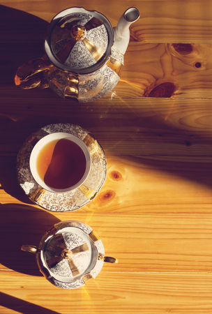 Top view of cup of tea on wooden plank table. Toned.