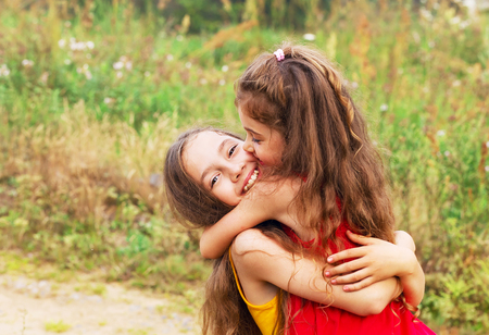 Two Cute little girls embracing and laughing at the countryside. Happy kids outdoors Stock Photo