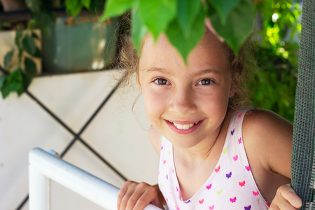 Portrait of beautiful teen girl smiling at the garden. Happy child