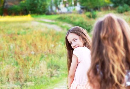 Beautiful young girl with long brunette hair, looking to camera at summer day. Having fun of joyful kid. Place for text