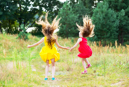 Two beautiful little girls  jumping and dancing at sunny summer day. Happy kids concept Stock Photo