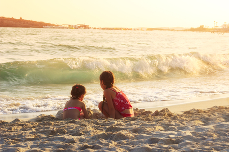 Two Cute Little Girls playing with sand by the Sea Waves at sunset.  Summer Sunny Day, Ocean Coast, happy Kids concept Stock Photo