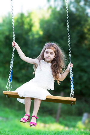Beautiful little girl sitting on swing at summer day, Happy childhood concept Stock Photo