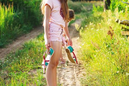 Beautiful teen girl is walking barefoot at sand road on warm summer day. Cute teen Girl feeling very happy on Summer background.
