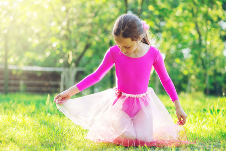 Beautiful preteen girl doing gymnastics and stretching in the city park on  summer sunset Stock Photo