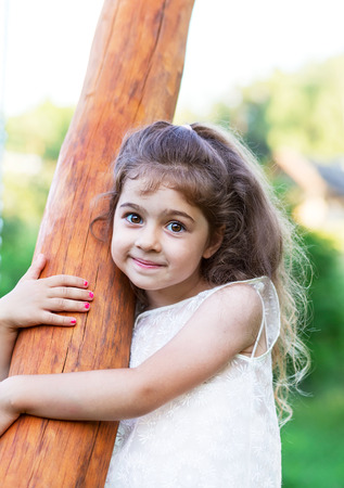 Portrait of smiling beautiful little girl at green of summer park.