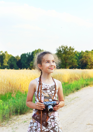 Cute little girl taking pictures with old film camera.  Pretty child in nature. Place for text Stock Photo