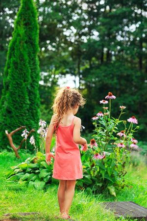 Cute little girl is standing and dreaming at the garden in warm sunny summer day