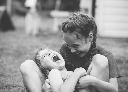 Two Happy little girls laughing and hugging at the  summer park. Black and white photo Stock Photo