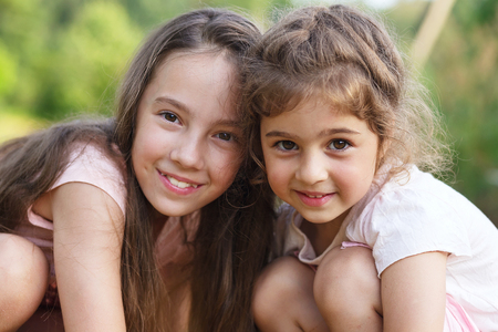 Two Happy little girls  hugging at the  summer park