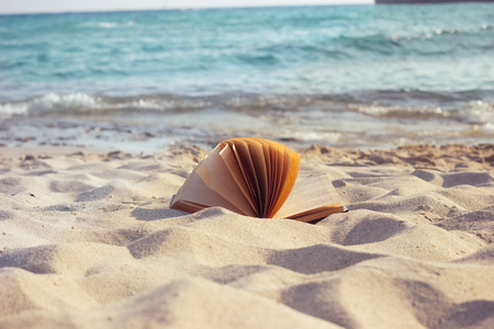 An open book laying on a sandy sunny beach at sunset.