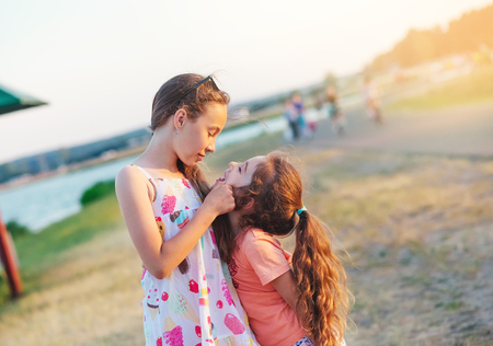 Two Happy little girls having fun and embracing  at meadow at summer day