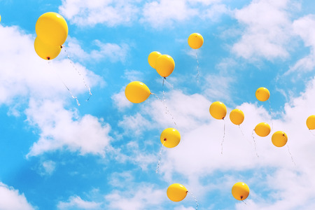 Balloons in the blue sky flying away. Toned, soft focused.