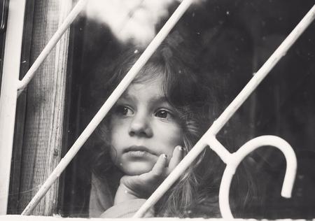 Black and white portrait of Sad little girl looks through window with lattice Stock Photo