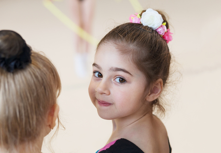 Little cute ballerina in studio looking on camera. Sport, training, fitness, stretching, dancing, yoga, active lifestyle concept