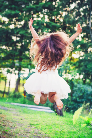 Beautiful little girl  Is jumping outside at  summer sunset