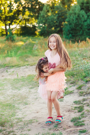 Two Happy little girls having fun and embracing  at sunny summer day