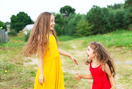 Two beautiful little girls playing and smiling at sunny summer day outdoors. Happy childhood concept Stock Photo