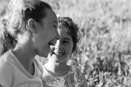 Two Happy little girls laughing and hugging at the  summer park. Happy chidhood concept. Black and white photo. Place for text