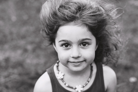 Black and white Portrait of cute little girl smiling outside Stock Photo