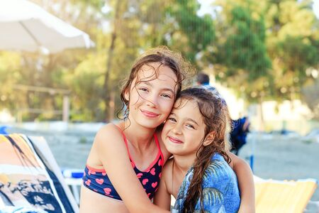 Two Cute Little Girls hugging and smiling at the Seaside at  Summer Sunny Day, Ocean Coast, happy Kids concept