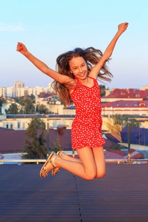 Portrait of a cute teenager girl  smiling and jumping outdoors at summer evening